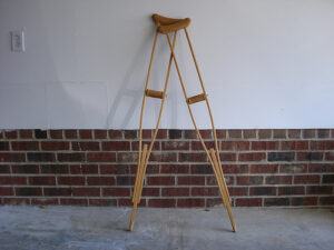 a picture of 2 crutches leaning against a wall - the top half of the wall is white paint, the bottom half is brick
