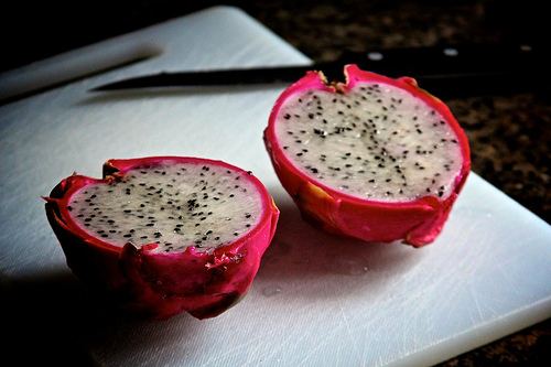 a dragon fruit split in half on a white plastic cutting board with a knife laid on the cutting board