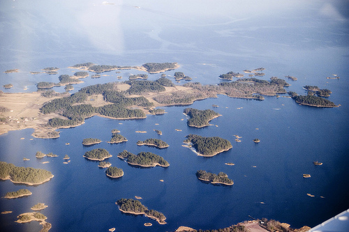 an aerial view of a string of forested islands