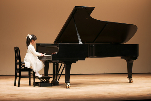 a young child wearing a white dress and a bow in her hair sitting at a baby grand playing at a piano recital