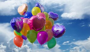 a cloudy sky full of balloons in a variety of colors, some of them oval shaped, some heart shaped