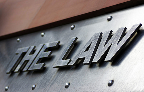 "a steel sign with raised letters that say ""THE LAW"" viewed from an angle"