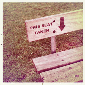 """a picture of a park bench with the words """"this seat taken"""" and a downward pointing arrow written on it"""