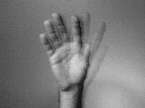 a black and white photo of a hand waving goodbye