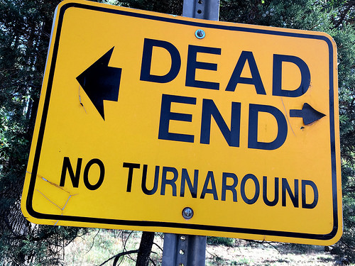 "a caution yellow sign that reads ""dead end no turnaround"" with arrows pointing to both the left and right"