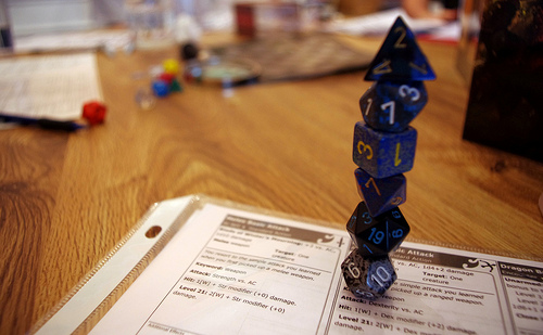 a tower of various blue dice (D4, D10, D12, D6, D20, etc) balanced so as to form a tower. They are on a character sheet for on a wooden table. The background is blurry but appears to have other dice.