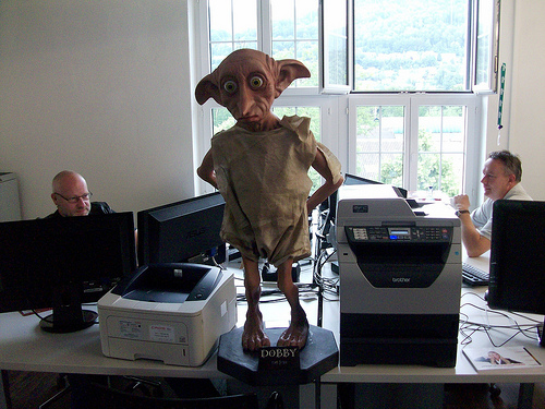 an office setting. Two men sit behind computer monitor in the background. In the foreground, a statue of Dobby the house elf from Harry Potter stands staring forward.