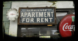 """a sign that reads """"furnished apartment for rent"""" in the center of the photo. On the left is a thermometer. On the right is a Coca-Cola sign."""