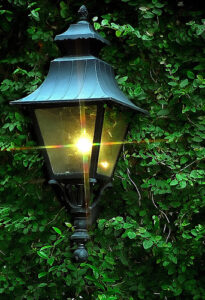 a lit gas lantern in New Orleans' French Quarter against a background of leaves
