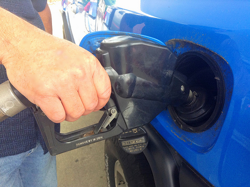 a hand using a gas pump to fill up a blue vehicle