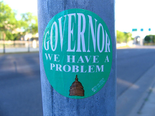 "a closeup of a circular green sticker stuck to a metal pole. The sticker reads ""Governor we have a problem"" and has a picture of a capitol building emblazoned at the bottom of it."