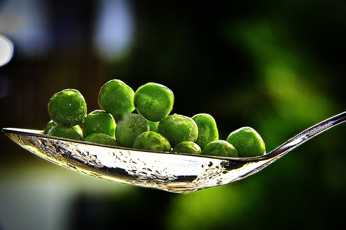 a closeup of a silver spoon loaded with green peas