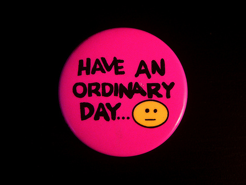 "a round pink button pin that reads ""Have an ordinary day..."" on it. There's an emoji with a neutral expression on it."