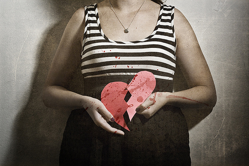 a person from the neck down wearing a necklace, black and white striped tank top, and black skirt. in their hands is a ripped up paper heart. there's a blood spatter pattern visible on their tanktop