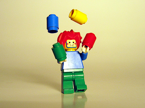 a tiny lego juggler with red hair, blue, shirt, green pants juggling 4 lego pieces, one in each of the following colors: blue, yellow, red, green