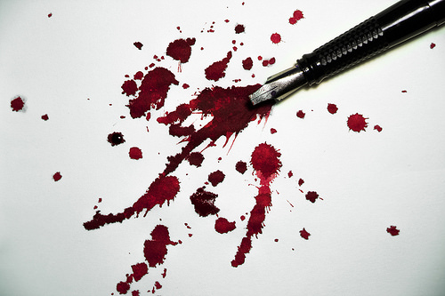 a black fountain pen splattering red ink all over a white sheet of paper