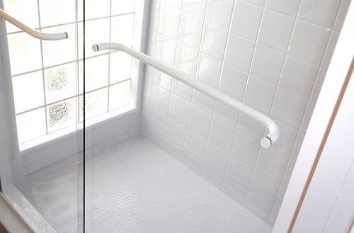 a glass walled tiled shower with a white stability bar