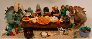 a long toy table set for a Thanksgiving meal flanked by several action figures including large trolls who sit on either end