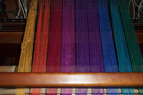 a weaving loom of a blanket in progress. The yarns used are multicolored. They are, from left to right: yellow, orange, red, pink, purple, blue, teal, green.