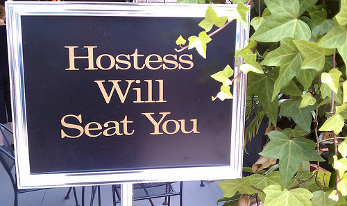 a sign that reads Hostess Will seat you. On the right side of the frame is some kind of leafy plant.