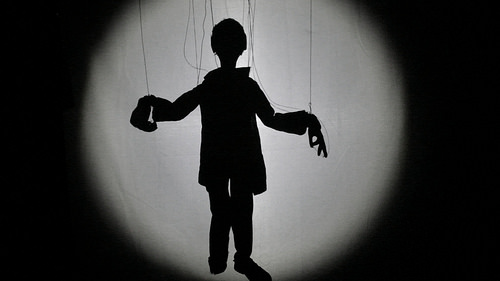 a shadowy silhouette of a marionette puppet with visible strings
