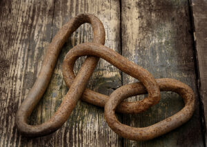 3 segments of rusty chain links on top of a wooden floor