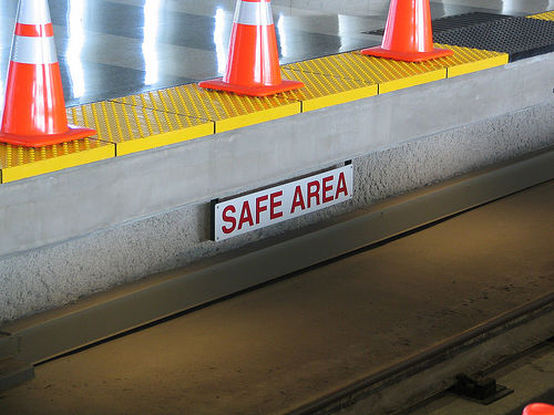 "a concrete barrier that has a sign on it that reads ""safe area."" The top of it has yellow currogated metal plates and some orange and white safety cones."