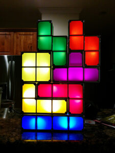 an illuminated Tetris themed lamp, with several 4-block structures of assorted colors locked together in a larger configuration
