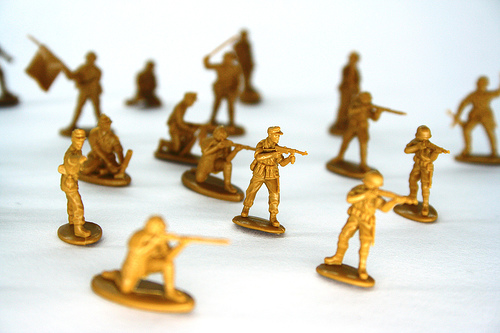 a closeup shot of about a dozen gold-colored toy soldiers in various positions: standing, crouching, etc
