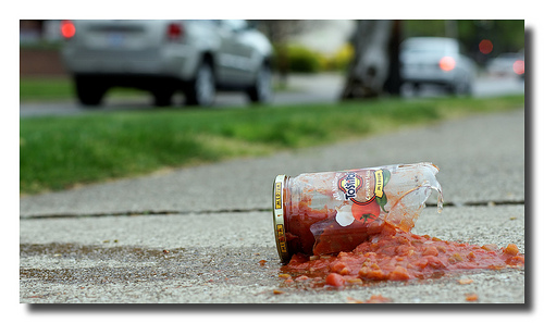 a broken glass jar of salsa that's been dropped on the pavement, a blurry line of cars is visible in the photo's background