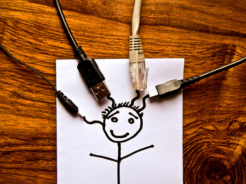 a stick figure person drawn on a sheet of typing paper with 4 connector cables attached to its head