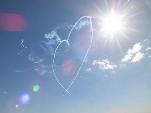 a photograph of a heart-shaped plane contrail with bright spots of sunlight