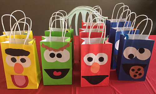 4 rows of gift bags. They appear to have the faces of 4 children's characters on them (left to right): Bert, Oscar the Grouch, Elmo, and Cookie Monster