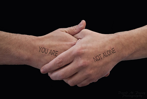 "A photograph of a handshake. The hand on the left has the words ""you are"" on it, and the hand on the right has the words ""not alone"" on it, so when read left to right, they read ""you are not alone."""