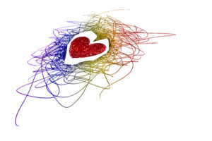 a heart inked in red surrounded by a mass of rainbow-colored squiggly ink lines
