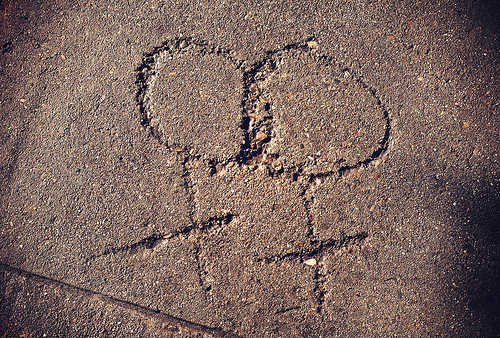 two interlinked woman symbols carved into a sidewalk