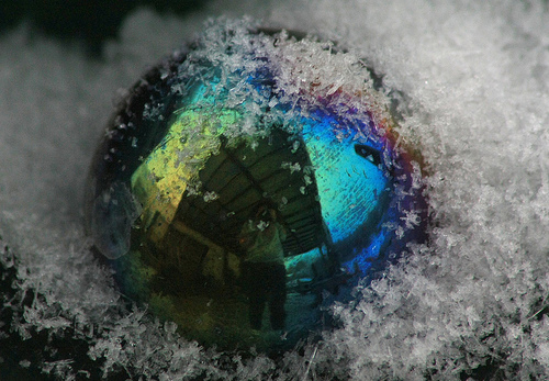 a pearlescent rainbow marble in the snow - you can see a distorted reflection of the photographer in it
