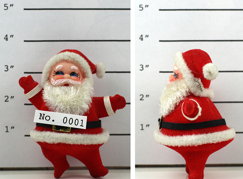 a photo of a toy Santa Claus taking mug shots in two positions