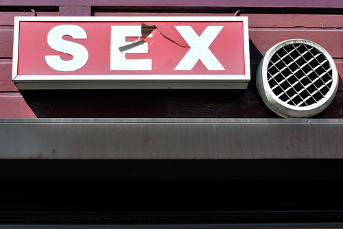 "a red sign with white lettering that reads ""sex."" The ""E"" has a crack through it."