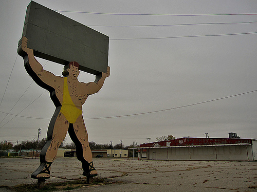 a statue of a carnival strong man in a yellow toga-like body suit and sandals hoisting a large block over his head