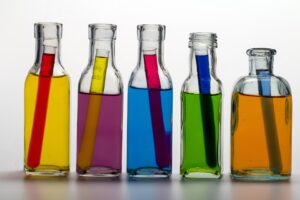 5 bottles with test tubes inside them. Colors of water within each container from left to right: Yellow bottle, red tube; purple bottle, yellow tube; blue bottle, red tube; green bottle, blue tube; orange bottle, light blue tube