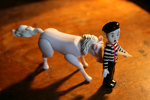 a toy unicorn goring a toy mime with its horn
