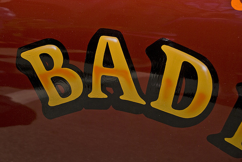 "the word ""bad"" painted on in yellow letters with a thick black outline on a shiny red surface"