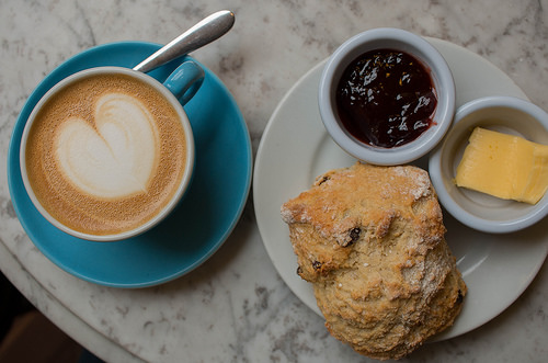 a cup of coffee with a milk foam heart design on the top of it served with a scone that has butter and jam next to it