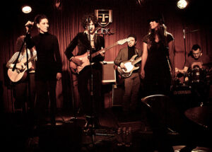 a picture of a jazz combo at a jazz club. There appear to be 2 vocalists, 2 guitarists, a bassist, and a drummer.