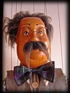 a wooden marionette puppet that appears to be a gray-haired old man with glasses and a bowtie, shot from the chest up