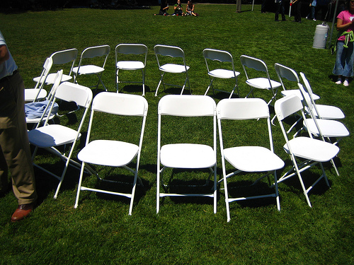 a bunch of white chairs formed in a circle with the seats facing outward, like in a game of musical chairs