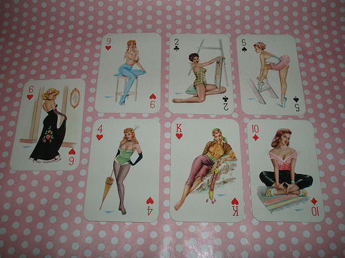 an assortment of Heinz Villiger pin-up playing cards displayed on a pink and white polka dotted tablecloth. They are starting from the 12 o'clock position and moving clockwise: A 2 of clubs taht portrays a woman in a polka dot bathing suit holding a painting and kneeling in front of a ladder, the 5 of spades which shows a woman in a tutu bending over on a ladder, the 10 of diamonds which shows a woman who is wearing a pink top with deep cleavage and a pair of black pants sitting cross-legged, the King of hearts which shows a woman leaning on her side who appears to be some kind of sexy pirate, the 4 of hearts which features a woman with a feather hairpiece and a green bathing suit and leggings who is carrying some kind of umbrella, the 6 of hearts which features a woman in a black dress with a flower on it who appears to be admiring herself in a mirror hanging on the wall, and the 9 of hearts which features a woman in a bikini top and blue pants sitting on some kind of 4-legged stool