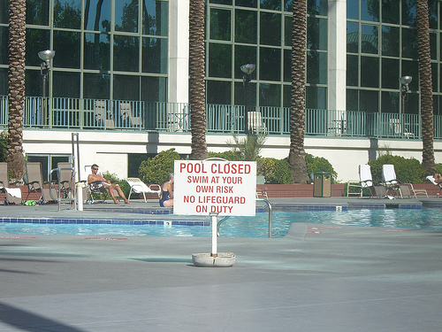 "a pool with sunbathers next to it in lounge chairs. A sign in the foreground reads ""Pool closed. Swim at your own risk. No lifeguard on duty."""