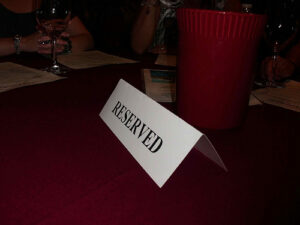 """a table with a sign on it that says """"reserved."""" next t the sign there is a red cup."""